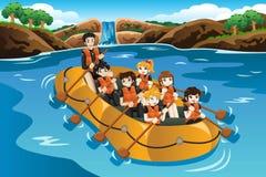 Niños que transportan en balsa en un río Imagen de archivo