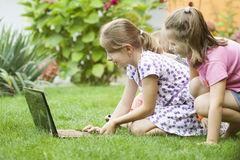 Niños que usan el ordenador portátil en el prado Fotos de archivo