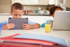 Niños que usan el ordenador portátil y la tableta de Digitaces para hacer la preparación Fotos de archivo
