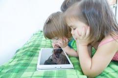 Niños que usan la tableta que miente en cama en casa Gasto del tiempo de los niños Niños usando la tableta imagen de archivo