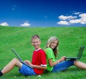 Niños que usan las computadoras portátiles afuera Foto de archivo libre de regalías