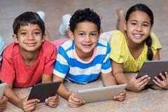 Niños que usan las tabletas digitales mientras que miente en piso Foto de archivo libre de regalías