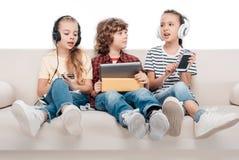 Niños que usan los dispositivos digitales Fotos de archivo