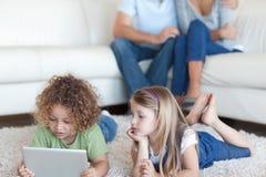 Niños que usan un ordenador de la tableta mientras que sus padres son watchin Fotos de archivo