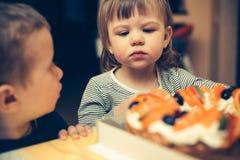 Niños que van a comer una torta Fotos de archivo libres de regalías