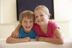 Niños que ven la TV con pantalla grande en casa Fotos de archivo libres de regalías