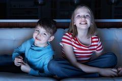 Niños que ven la TV junto el sentarse en el sofá Imagen de archivo