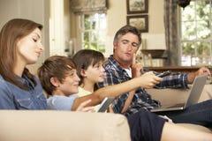 Niños que ven la TV mientras que los padres utilizan el ordenador portátil y la tableta en casa imagen de archivo