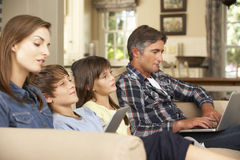 Niños que ven la TV mientras que los padres utilizan el ordenador portátil y la tableta en casa Foto de archivo libre de regalías