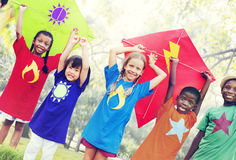 Niños que vuelan concepto juguetón de la amistad de la cometa Foto de archivo