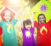 Niños que vuelan concepto juguetón de la amistad de la cometa Fotos de archivo