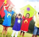 Niños que vuelan concepto juguetón de la amistad de la cometa Fotos de archivo libres de regalías
