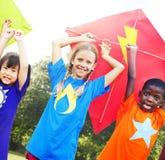 Niños que vuelan concepto juguetón de la amistad de la cometa Fotografía de archivo libre de regalías