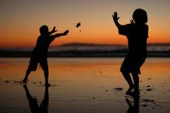 Niños silueteados que juegan en la playa Foto de archivo