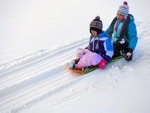 Niños Sledding abajo de la colina de la nieve en velocidad rápida del trineo Foto de archivo libre de regalías