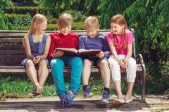 Niños sonrientes agradables que se sientan en el banco Fotografía de archivo