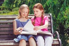 Niños sonrientes agradables que se sientan en el banco Foto de archivo libre de regalías