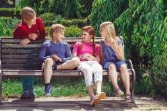 Niños sonrientes agradables que se sientan en el banco Imagen de archivo libre de regalías
