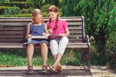 Niños sonrientes agradables que se sientan en el banco Fotos de archivo libres de regalías