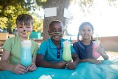 Niños sonrientes con la pintura de la cara que tiene bebidas en el parque Fotografía de archivo