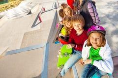 Niños sonrientes con los monopatines y los cascos Fotos de archivo