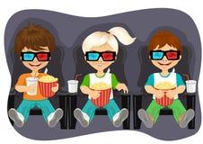 Niños sonrientes con palomitas que miran la película 3D Imagen de archivo