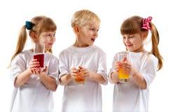 Niños sonrientes con un vidrio de jugo Fotos de archivo libres de regalías
