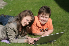 Niños sonrientes con una computadora portátil Fotografía de archivo