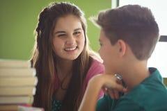 Niños sonrientes de la escuela que obran recíprocamente en biblioteca Imágenes de archivo libres de regalías