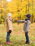 Niños sonrientes en parque del otoño Fotografía de archivo