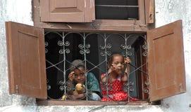 Niños sonrientes en ventana Fotografía de archivo