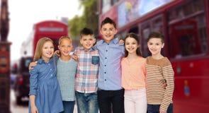 Niños sonrientes felices que abrazan sobre la ciudad de Londres Fotos de archivo libres de regalías