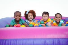 Niños sonrientes lindos en piscina de la bola de la esponja Imagen de archivo