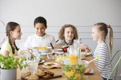 Niños sonrientes que comen la cena mientras que celebra imagen de archivo