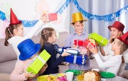 Niños sonrientes que dan los regalos al muchacho del cumpleaños Imagen de archivo
