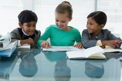 Niños sonrientes que discuten en la sala de reunión Fotografía de archivo
