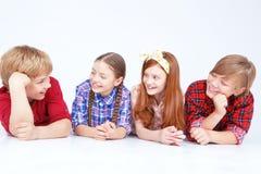 Niños sonrientes que mienten en el piso en crudo Foto de archivo