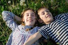 Niños sonrientes que mienten en la hierba que goza de Sunny Spring Day Fotografía de archivo libre de regalías