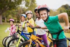 Niños sonrientes que presentan en crudo con las bicis Fotos de archivo