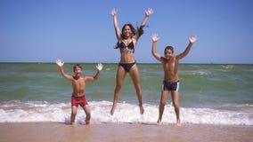 Ni?os sonrientes que saltan en la playa en la resaca almacen de video