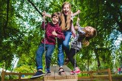 Niños sonrientes que se divierten en el patio Niños que juegan al aire libre en verano Adolescentes que montan en un oscilación a Fotografía de archivo
