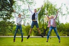 Niños sonrientes que se divierten y que saltan en la hierba Niños que juegan al aire libre en verano los adolescentes comunican a Fotos de archivo libres de regalías