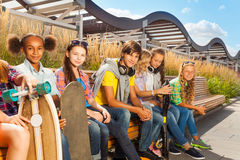 Niños sonrientes que se sientan en banco de madera juntos Imágenes de archivo libres de regalías