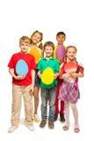 Niños sonrientes que sostienen tarjetas coloridas de la forma del huevo Imagen de archivo libre de regalías