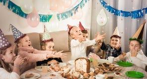 Niños sonrientes que tienen un buen rato en una fiesta de cumpleaños Imagen de archivo