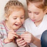 Niños sorprendidos con el teléfono móvil Foto de archivo libre de regalías