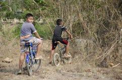 Niños tailandeses biking la bicicleta en el sepulcro del chino del cementerio de Sritasala imagen de archivo libre de regalías