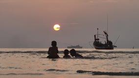 Niños tailandeses silueteados en la vida real que juegan y que salpican en el mar en la puesta del sol metrajes
