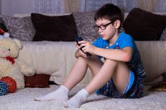 niños, tecnología, comunicación y concepto de la gente - muchacho de Internet con el mensaje que manda un SMS del smartphone o el imagen de archivo libre de regalías