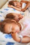 Niños tres junto que duermen en cama Imagenes de archivo
